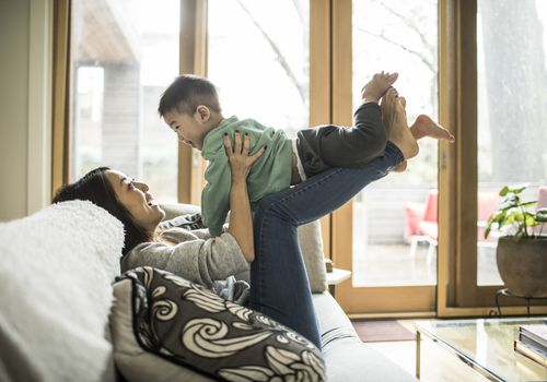 Mother on sofa with her toddler perched on her legs