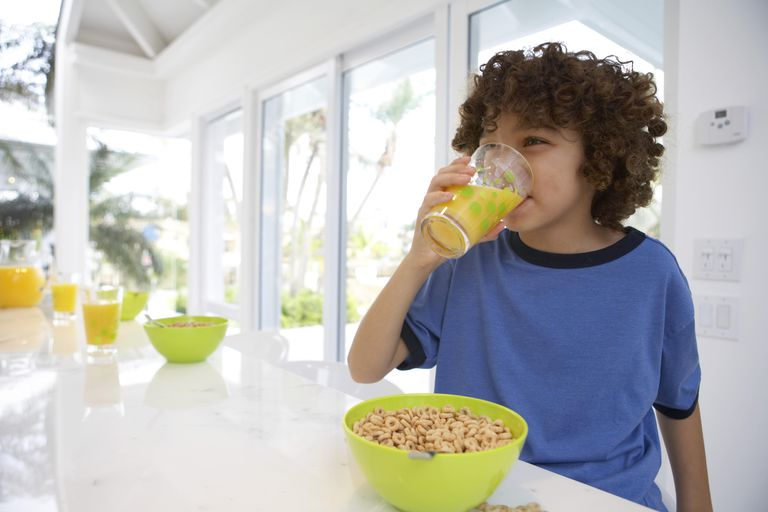 Boy (8-10) at table, drinking orange juice