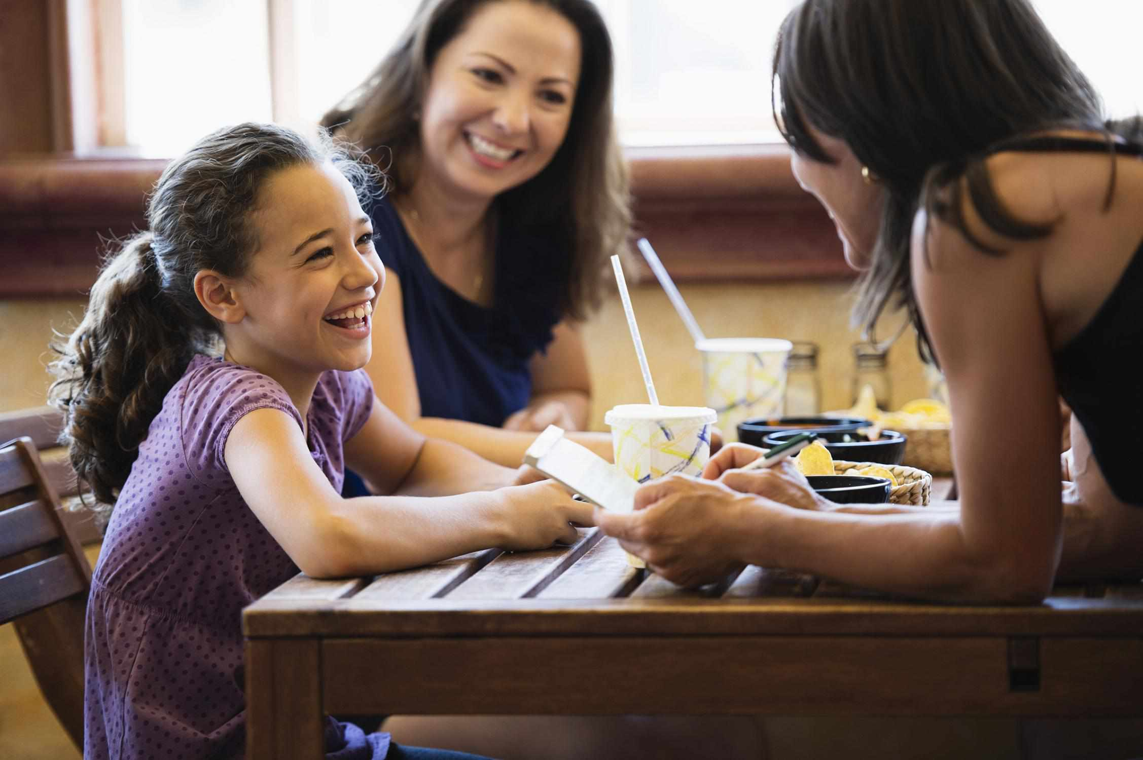 child ordering at a restaurant with her mother