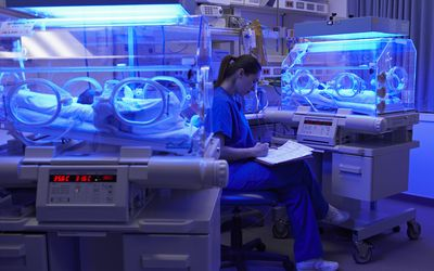 Neonatal Intensive Care Unit With Babies Under UV Lights And Nurse Taking Notes