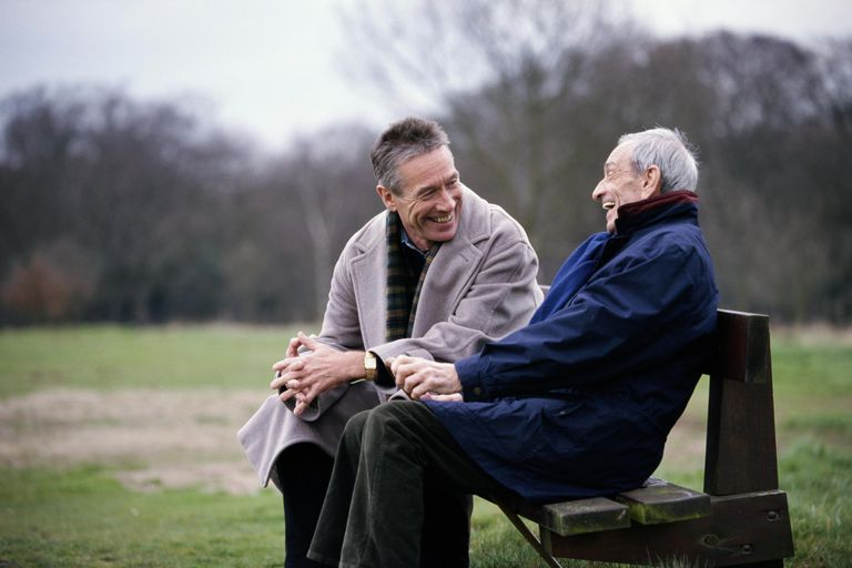 elderly man laughing with his adult son on a park bench