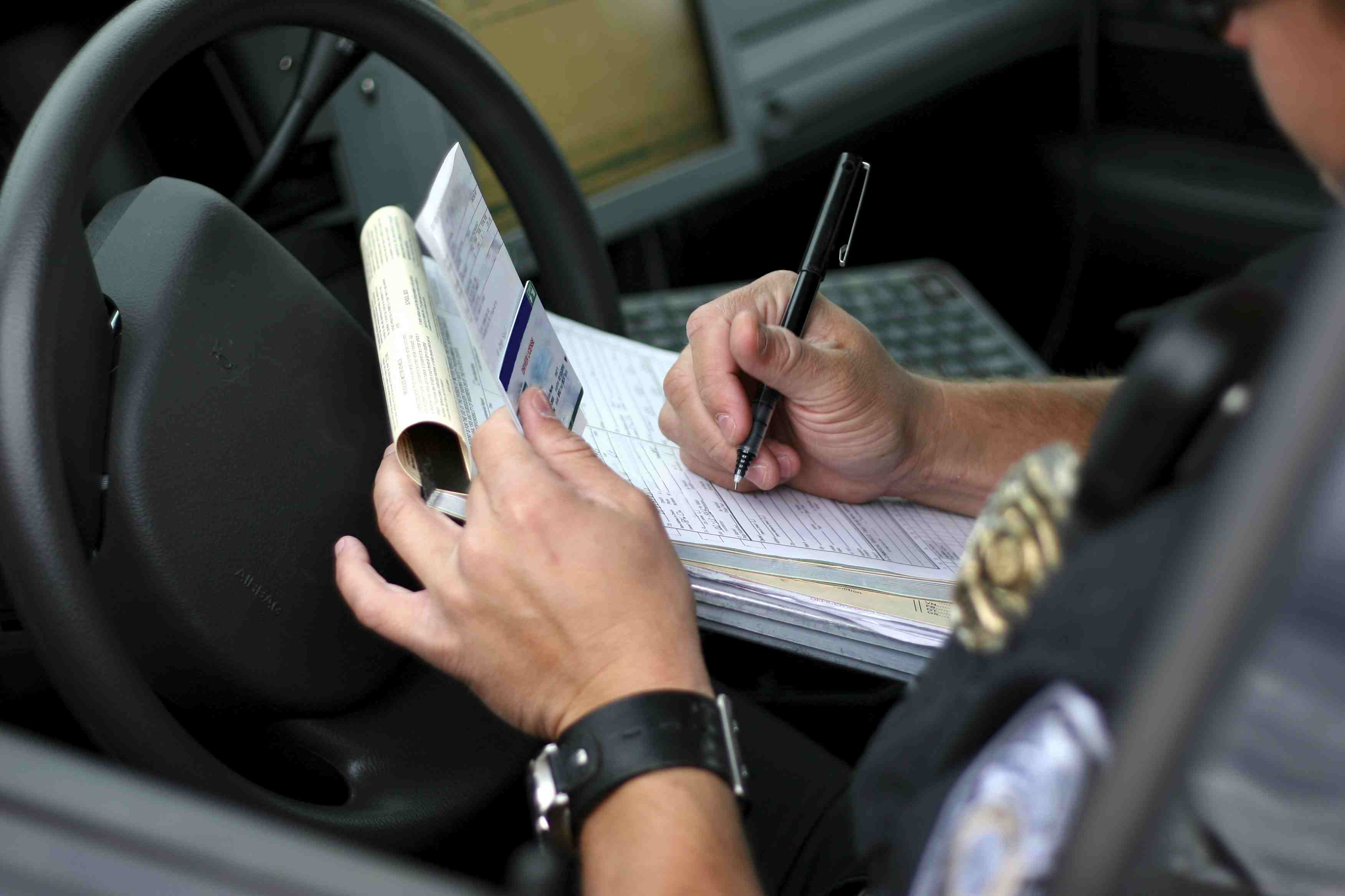 Police officer writing out ticket for speeding, high testosterone levels increases risk taking behaviors like speeding