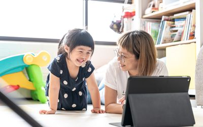 Mother using tablet watching videos happily with young daughter