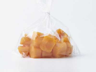 Frozen pureed carrot cubes in tied-up transparent plastic freezer bag