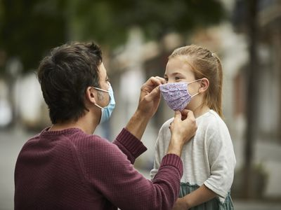 Dad wearing a mask putting a mask on a child