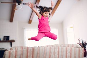 A little girl jumping on the furniture