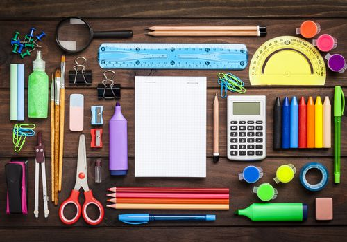 Top view of a large group of school or office supplies on wooden table