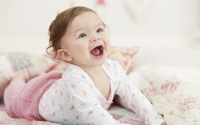 Smiling baby in pink pants with floral top pushing up from the ground