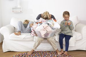 Exhausted mother with laundry basket shows that parenting is hard and tiring