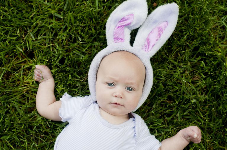 Baby lying in grass wearing Easter bunny ears.