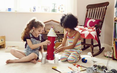 two girls work together to build a rocket ship