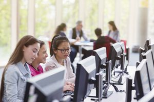 Girl students studying at computer in library