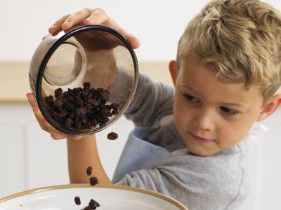 Boy pouring raisins into bowl of muesli mixture, 4 years