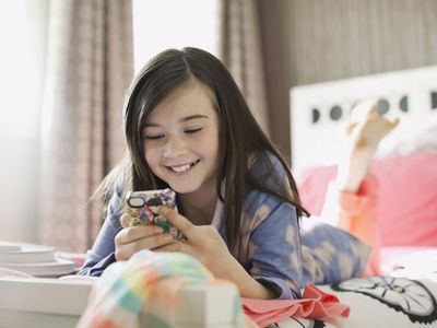 Smiling girl using smart phone in bed