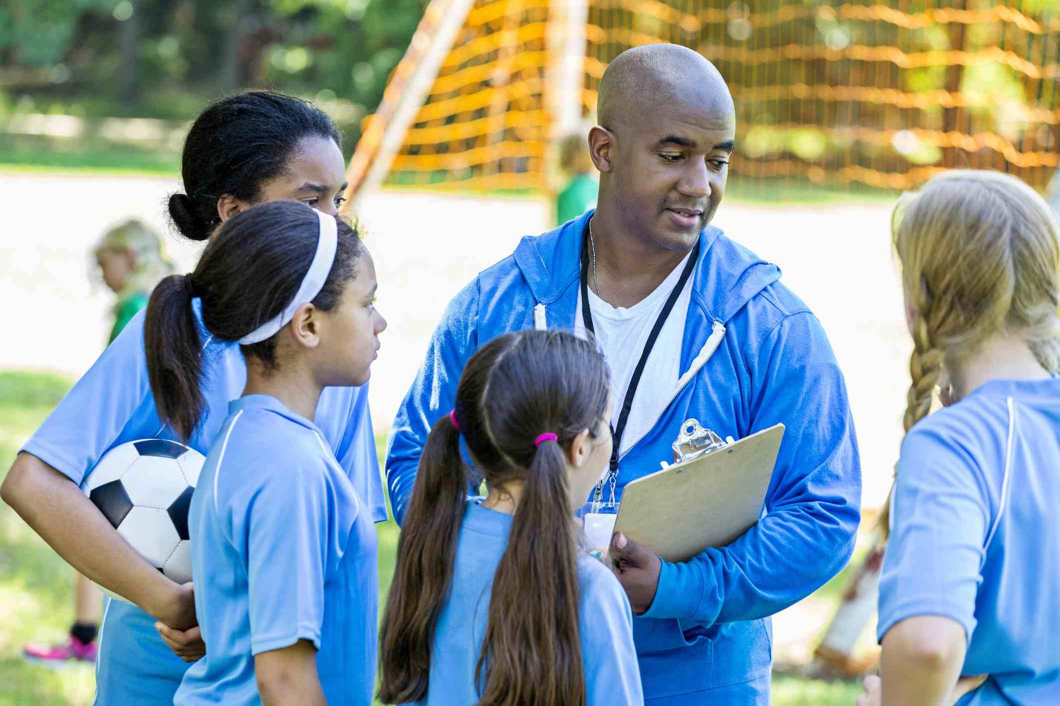 Girls talking to male soccer coach