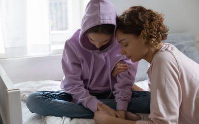Mother comforting upset teenage daughter.