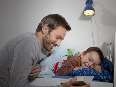 Father reading to his son at bedtime