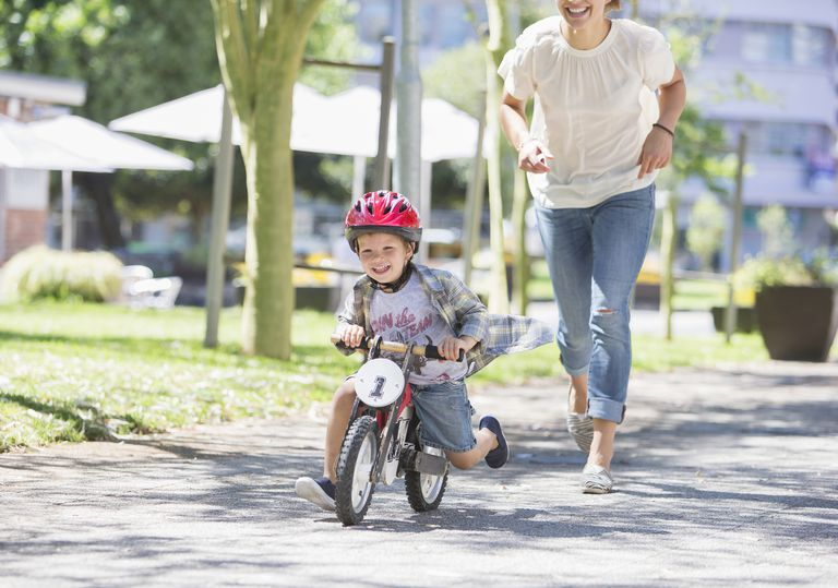Mother chasing son riding bicycle with helmet in sunny park