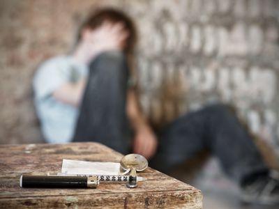 Drug paraphernalia with blurred teen sitting in background