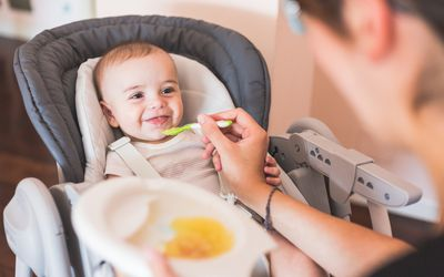 Mother feeding baby boy with spoon