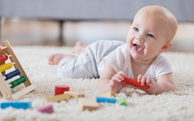 Cute baby sings with open mouth while playing with wooden blocks