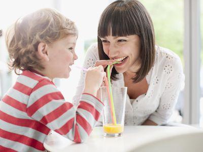 mom drinking orange juice with toddler boy