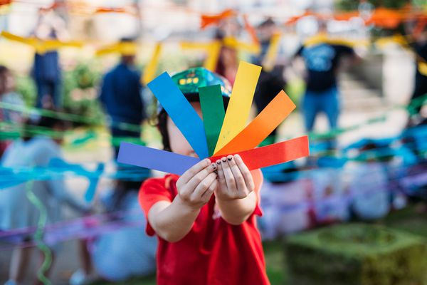 child holding rainbow colored papers PRIDE
