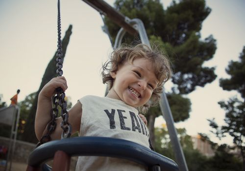 Toddler on a swing laughing