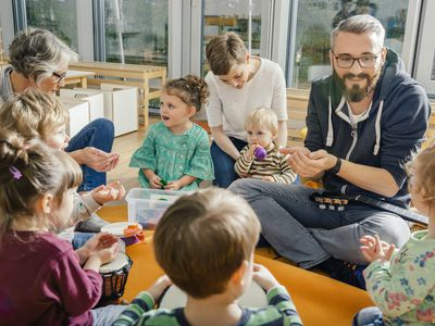 Children and teachers playing and making music in kindergarten