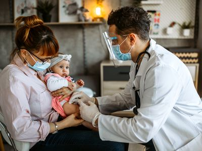 A mom wearing a mask holds her baby as a doctor gives her a vaccine in her leg.