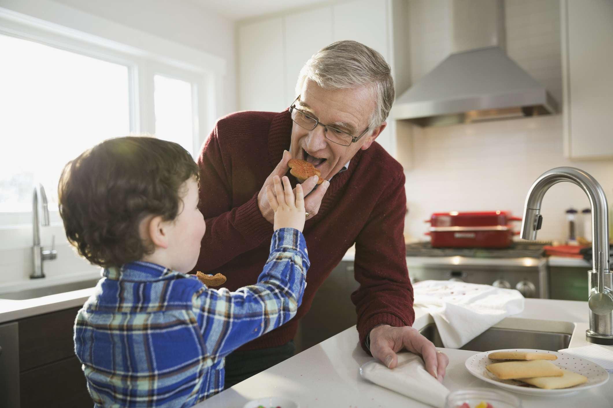 Boy feeding Christmas cookie to grandfather