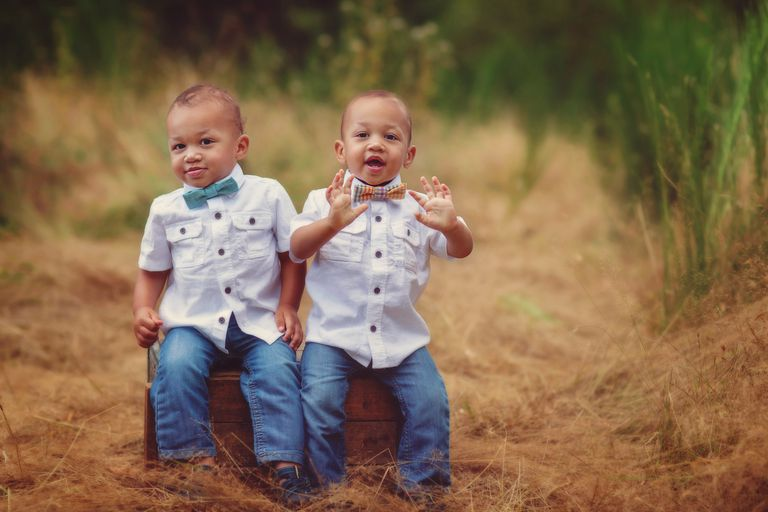 Twin toddlers in matching outfits sitting on a box in a field