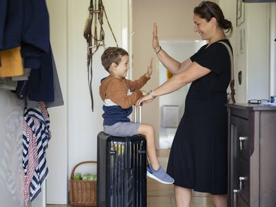 Boy with suitcase high-fiving woman