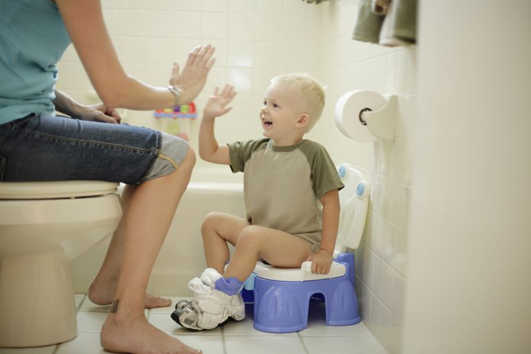 Child on toilet with parent encouraging them