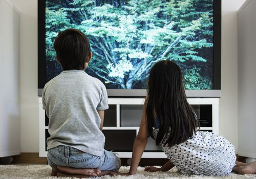 Boy and girl watching TV up close