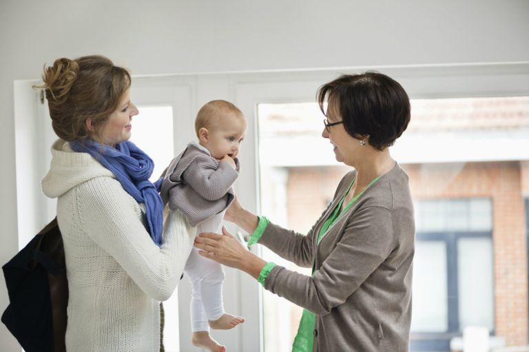 mom handing infant over to babysitter