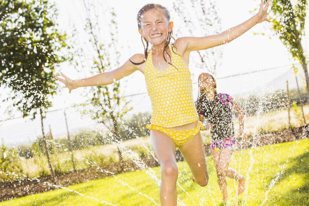 girls running through sprinklers