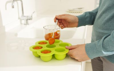 a person spooning pureed baby food in tray for freezing