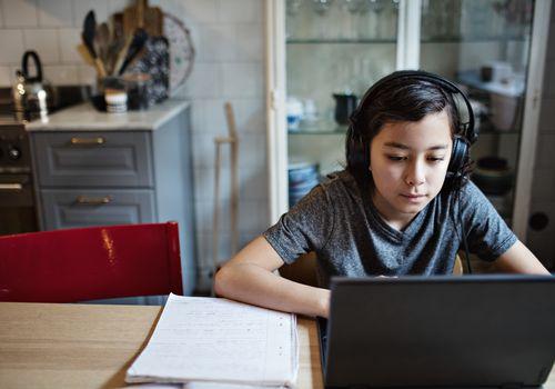 Boy wearing headphones while using laptop during homework at home