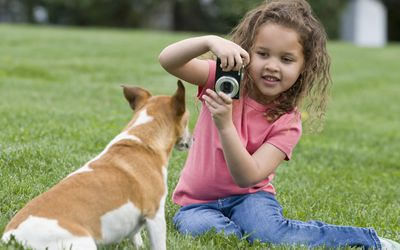A girl using a camera outside.