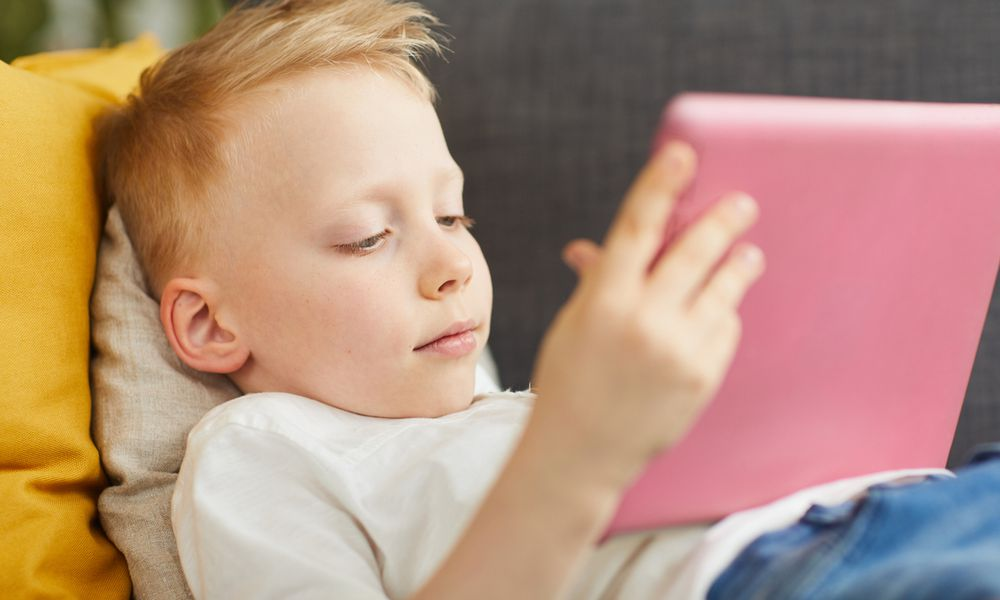 young boy on couch with iPad