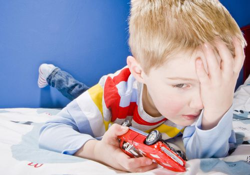 Upset young boy with toy car