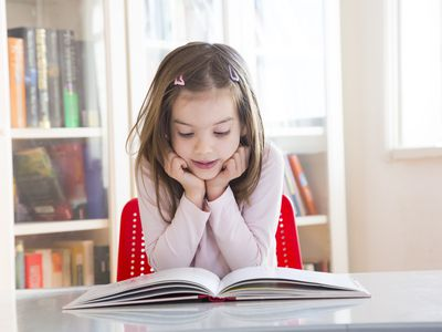 second grade girl reading a book on a table