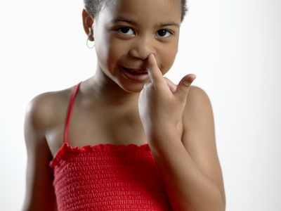A little girl picking her nose