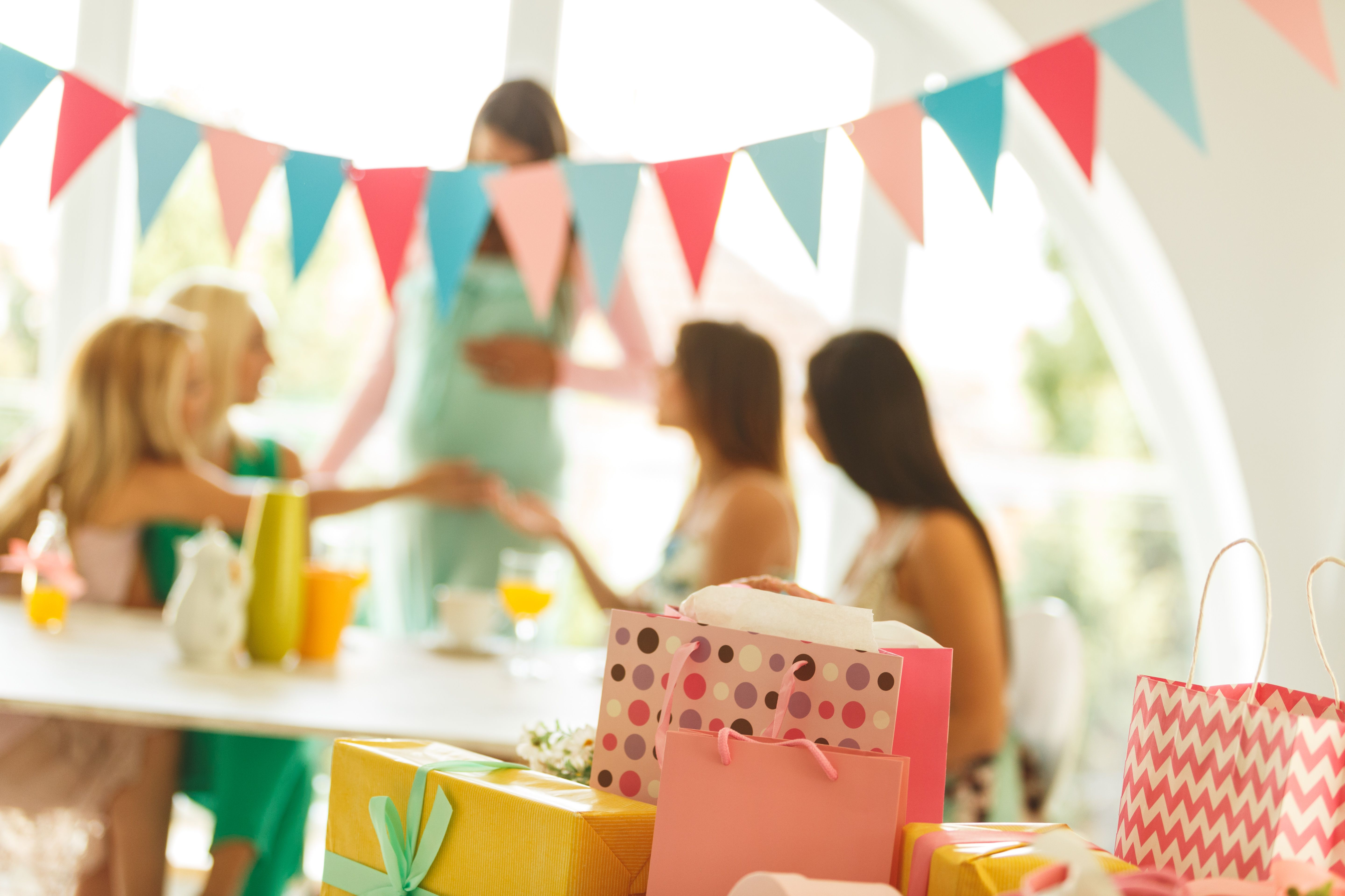 Presents at baby shower party with women celebrating in the background