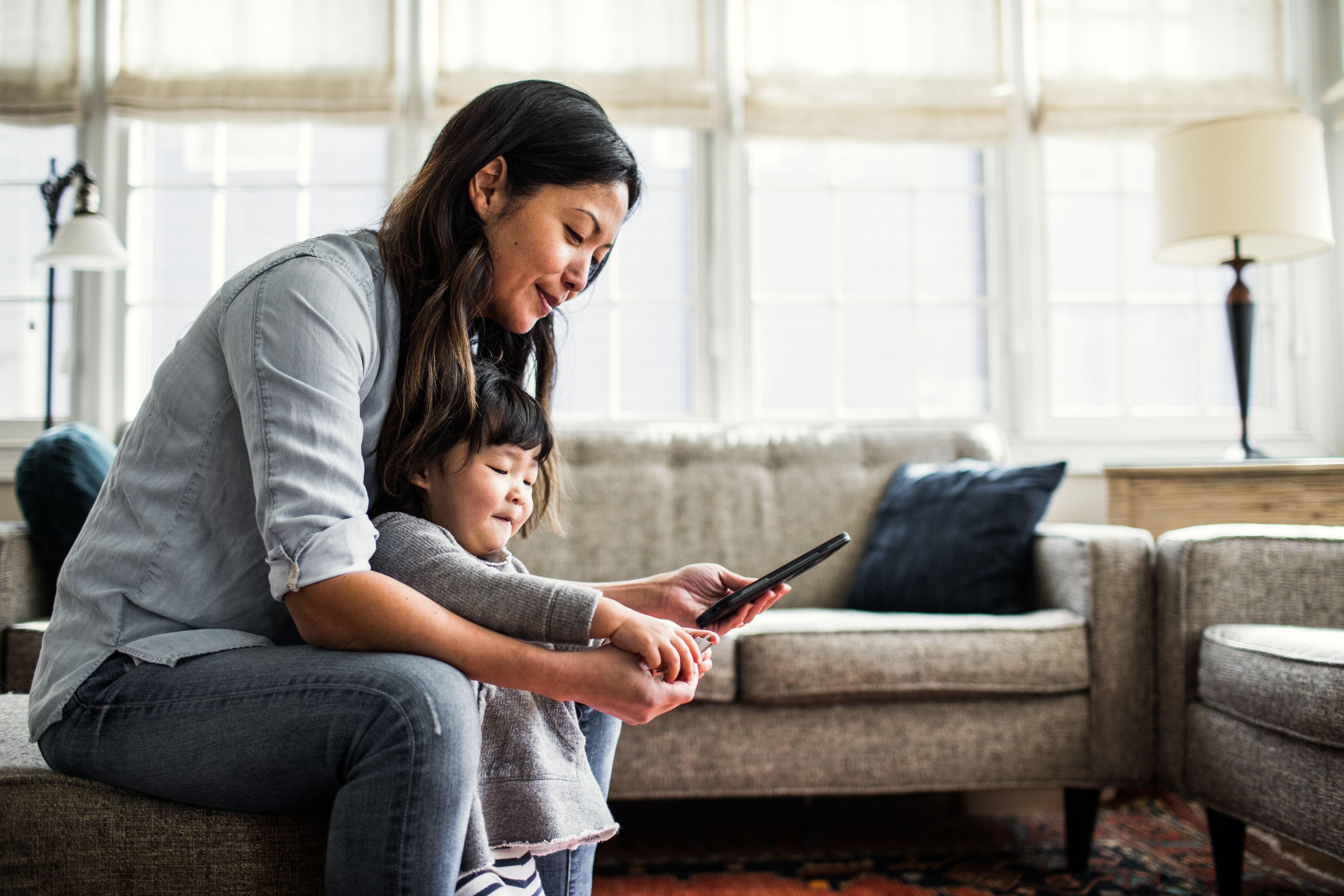 Woman using smartphone with a child standing between her legs