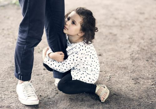 Daughter gripping fathers leg while sitting on ground at park