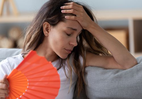 Close up of a woman sitting on a couch using a fan
