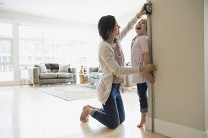 A mother measuring her daughter's height against a wall