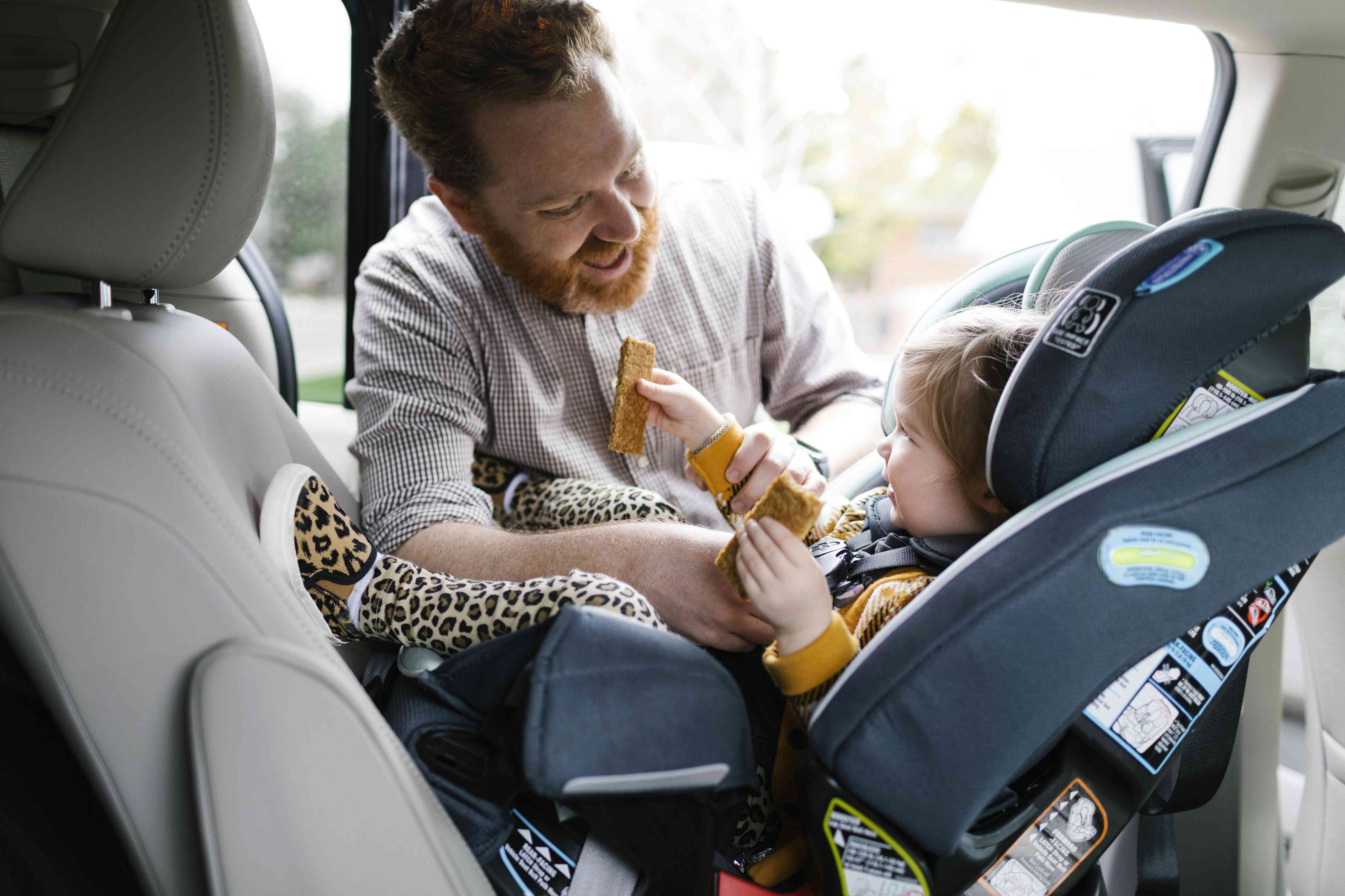 Father buckling toddler in car seat with a snack